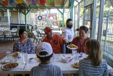 Elia Montoya serves breakfast dishes to U.S. Representative Chip Roy and his family at Juan In A Million, located in East Austin, on May 1, 2020. This was the first phase of Gov. Greg Abbott's order to gradually reopen Texas businesses during the coronavirus outbreak.