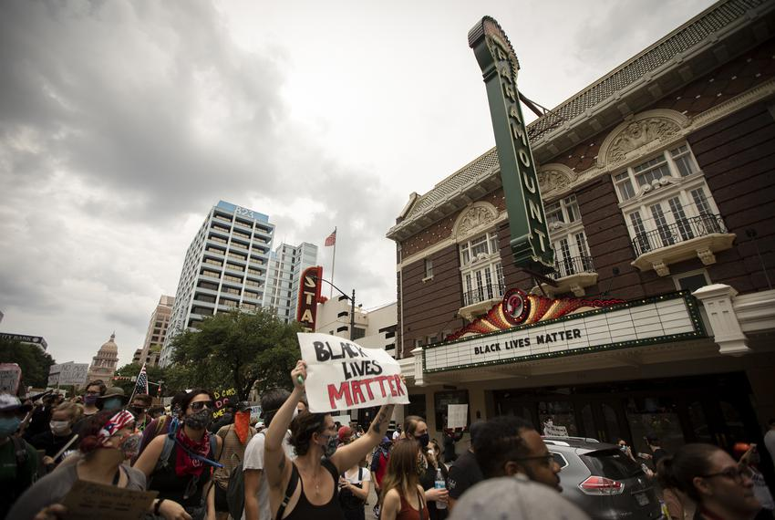 A group of protesters march south on Congress Avenue in downtown Austin. The group marched in protest of the killing of Ge...