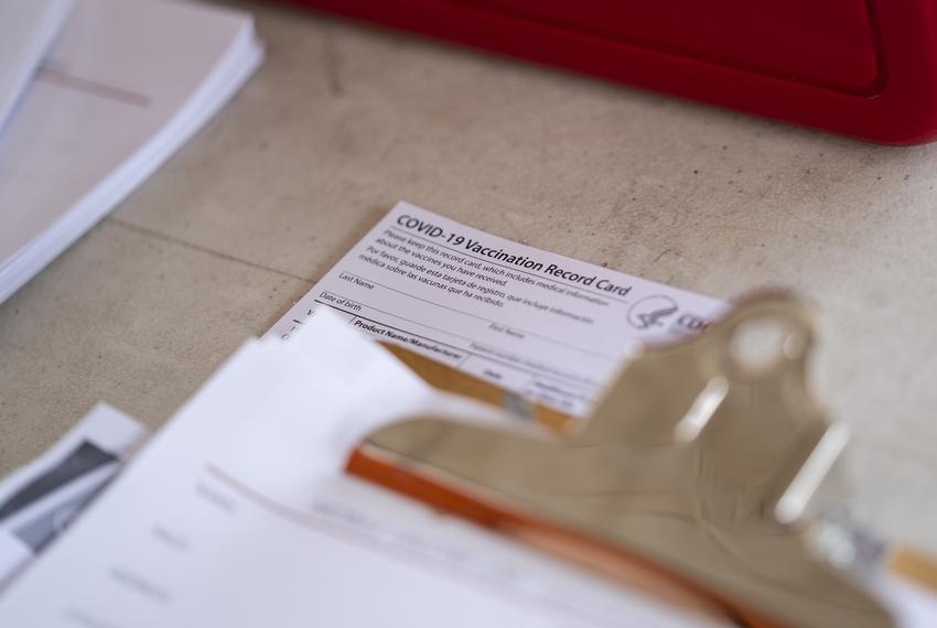 A COVID-19 Vaccination Record Card sits on a table at a vaccine clinic held in partnership between the Central Texas Food Ba…