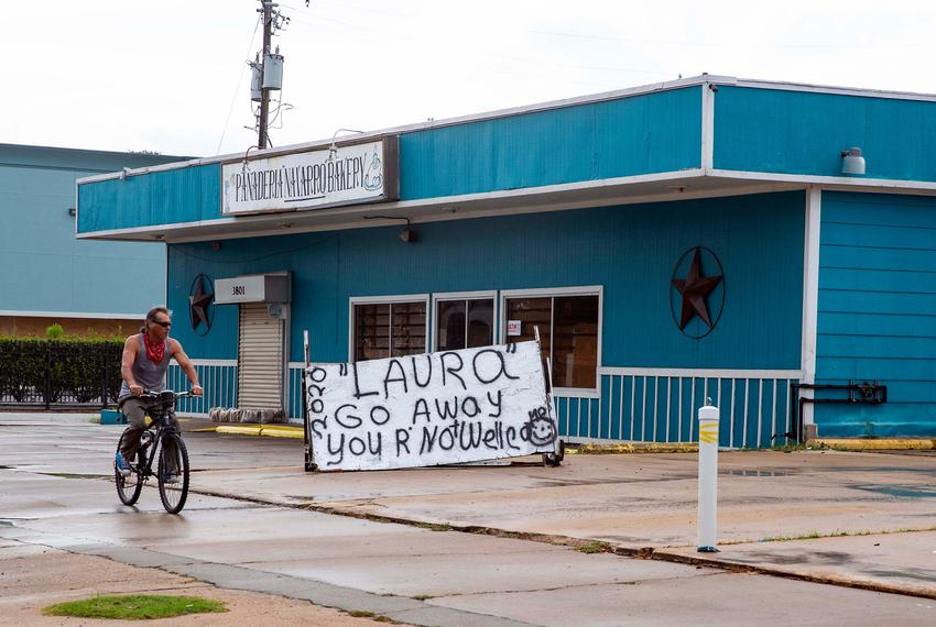 """A man rides a bike down Broadway Street in Galveston, past a sign that reads """"Laura Go Away your' not welcome."""" Hurricane La…"""