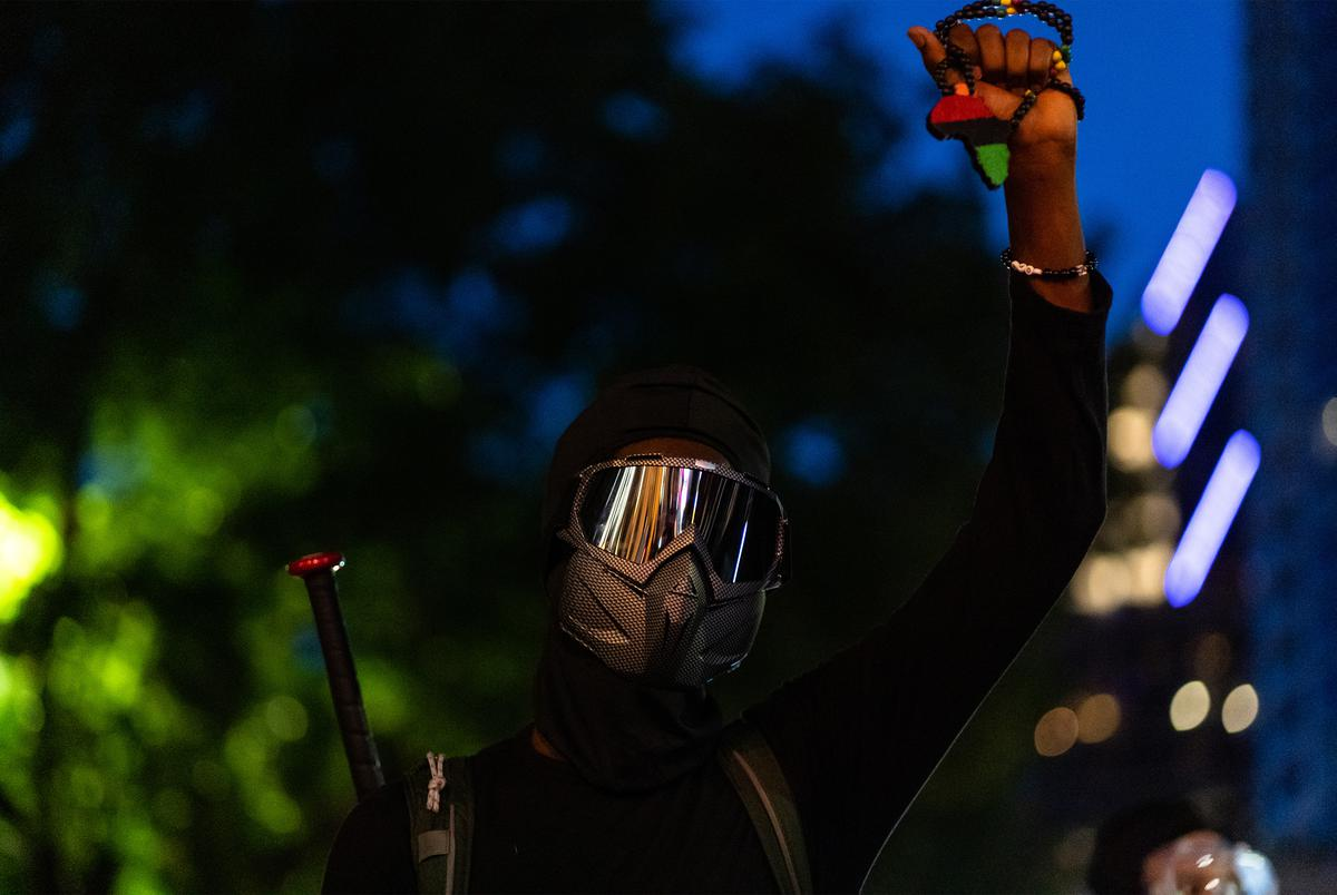 A protester armed with a baseball bat kneels in the street with fist upraised as protesters clashed with police in downtown Austin on Aug. 1, 2020.