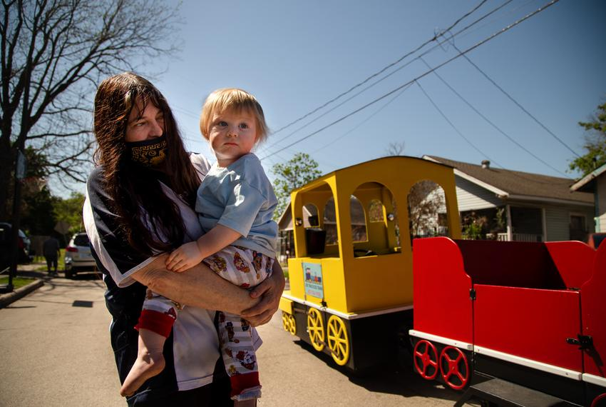 Lucille Hammash holds her grandson, Kenny Proctor, as they watch a trackless party train drive by their neighborhood in cent…