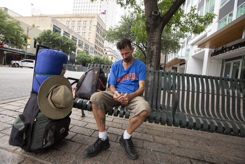 Daniel Johnson, who is homeless, sits on a bench on Congress Avenue in downtown Austin on Aug. 4, 2019.