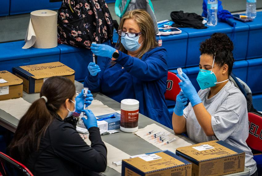 Medical workers load up syringes with vaccines for COVID-19 at the Delco Activity Center in Northeast Austin, on March 13, 2…