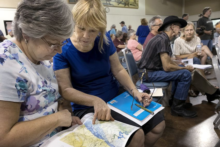 Hays County residents Ann Arendarczyk, left, and Leigh Peterson look at water resource maps during a public meeting on June 18 at the Wimberley Community Center, where concerned residents learned about Electro Purification's proposed permit to pump up to 2.5 million gallons of water daily from the Trinity Aquifer.