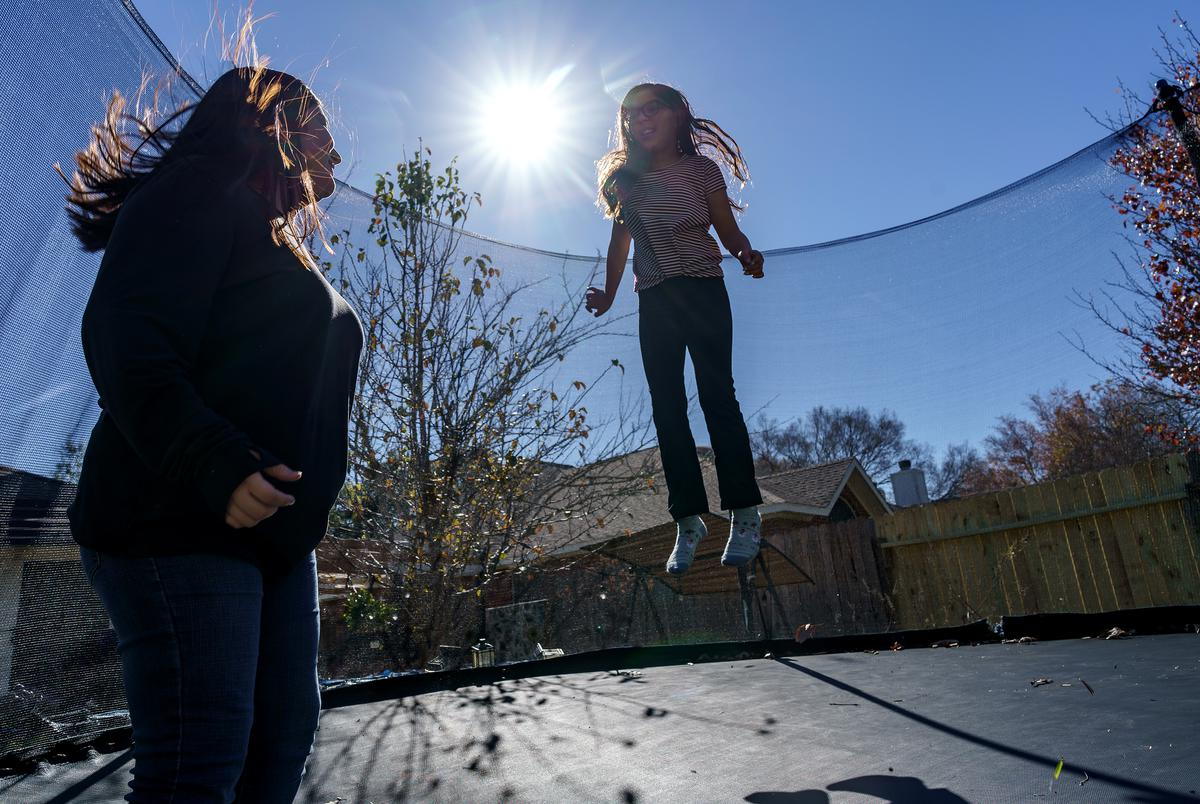 Isabel Suarez, left, and her sister, Llana Ramos, right, take a break from their virtual schooling to jump on the trampline in their backyard on Dec 9, 2020.