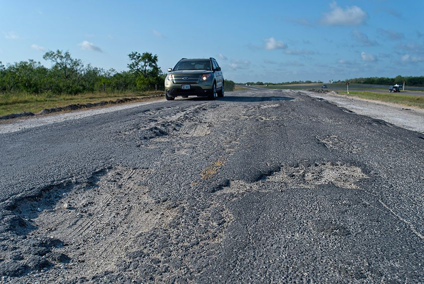 A driver maneuvers around a badly damaged portion of the IH 37 frontage road south of FM 99 in Live Oak County, TX on Firday, August 16, 2013