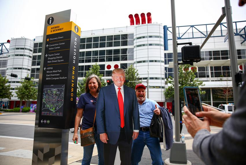 J.R. Roberts, left, poses with a fellow supporter and her cardboard cutout of President Trump for a picture in Houston, on O…
