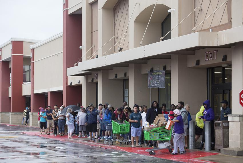 People line up for food at an open grocery store in Houston Tuesday Aug 29, 2017.