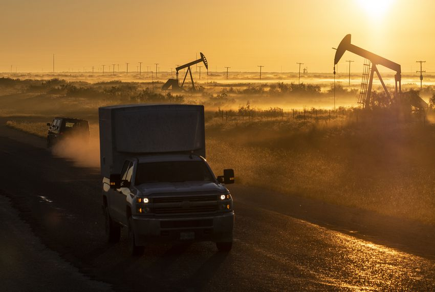 Vehicles pass oil pumpjacks at sunrise in the Permian Basin region of West Texas.