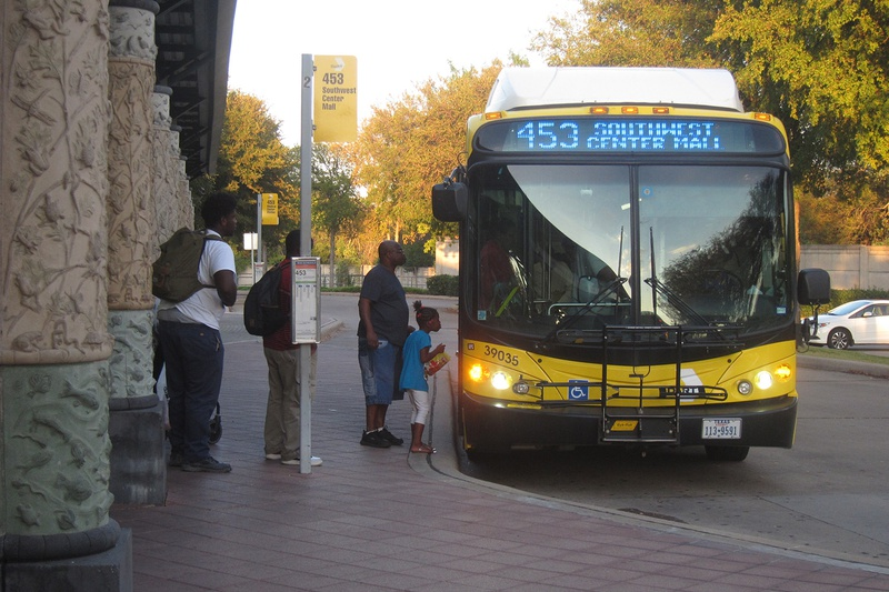 Dallas Area Rapid Transit passengers board a bus at the Hampton Station in October 2016.
