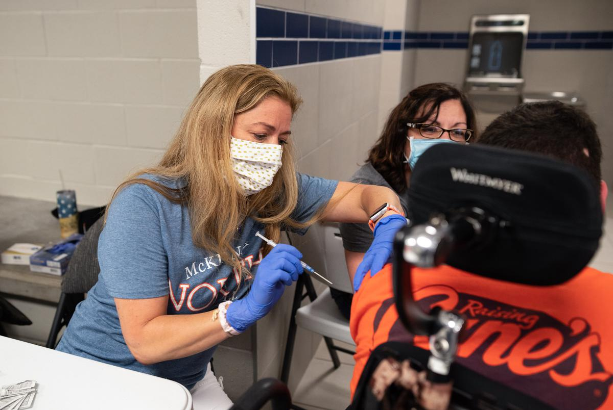 McKinney ISD registered nurse Stephanie Martin administers a COVID-19 vaccine to a 17-year-old at the McKinney ISD Stadium and Community Event Center on May 20, 2021.