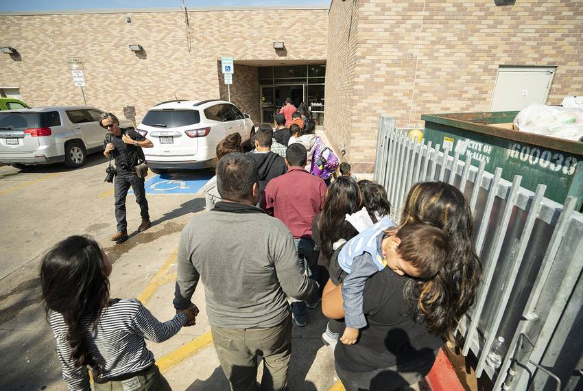 Immigrants, many wearing ankle monitors, are dropped off at the McAllen Central Station, where they are they are given bus tickets to other parts of the cou...