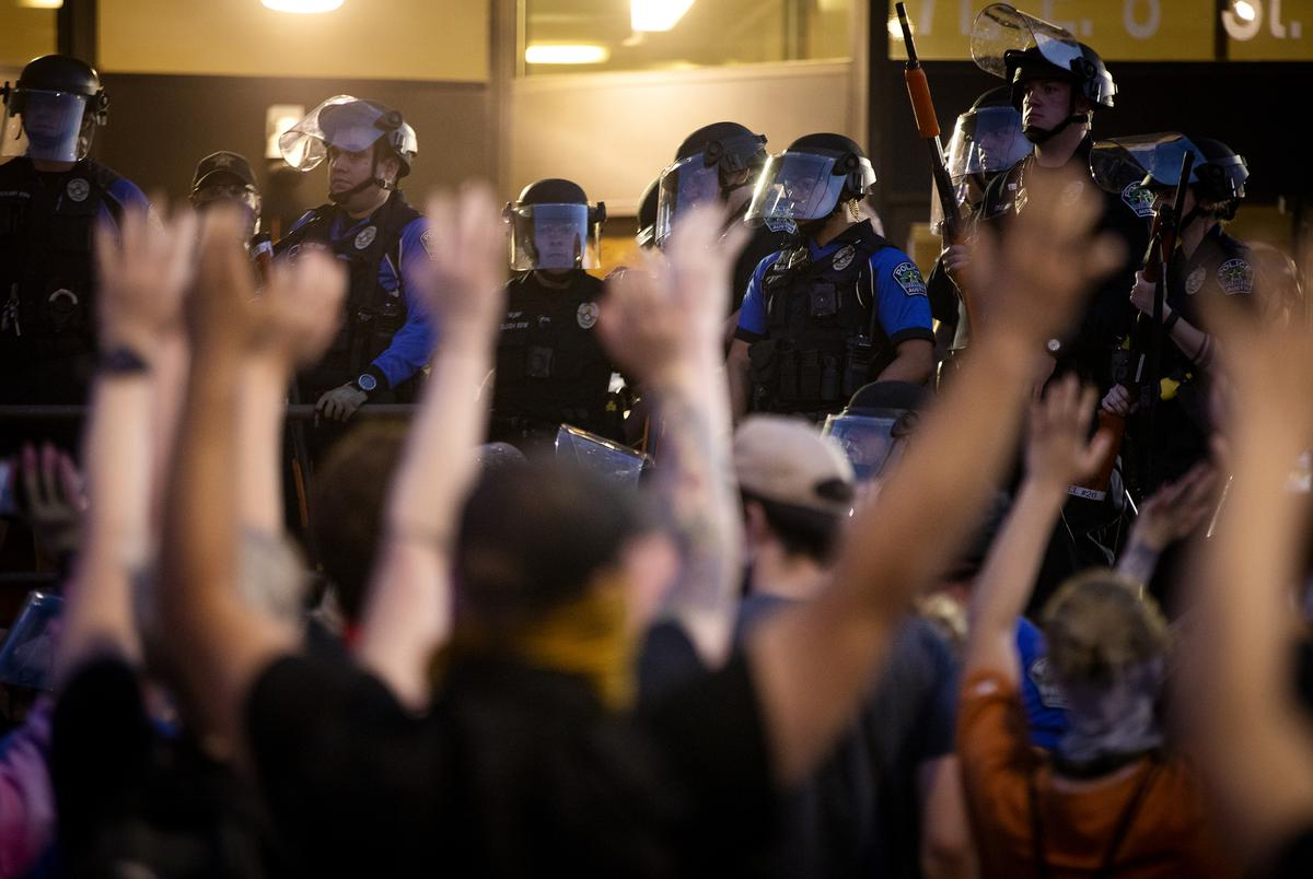 """Protesters raise their arms and chant, """"Don't shoot!"""" after Austin police officers fired tear gas and rubber bullets at the crowd. May 30, 2020."""