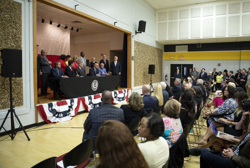 Lt. Gov. Dan Patrick (front, second from left), Gov. Greg Abbott and House Speaker Dennis Bonnen speak at a press conference on the $11.6 billion school finance reform bill. Abbott signed the bill into law Tuesday at Parmer Lane Elementary School in Austin.