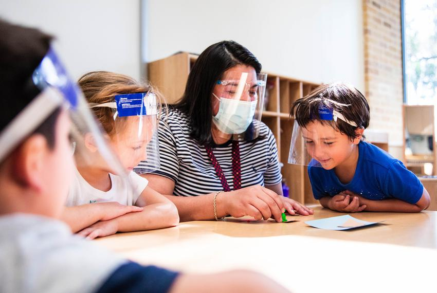 Pre-K 4 SA teacher Charlene Flores works with students learning in-person during the COVID-19 pandemic.