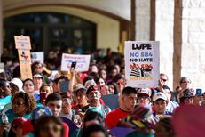 """People demonstrating against Senate Bill 4, the """"sanctuary cities"""" ban, march near the Riverwalk in San Antonio on June 26, 2017. U.S. District Judge Orlando Garcia heard opening argumentsfrom Texas cities and counties challenging the measure, signed into law by Gov. Greg Abbott."""