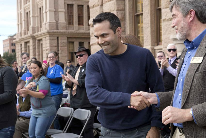 Land Commissioner George P. Bush shakes hands with Texas Alliance for Life Director Joseph Pojman at the Texas Capitol on Ja…