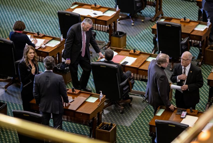 Maskless lawmakers speak to one another on the Senate floor prior to the session beginning on March 2, 2021.