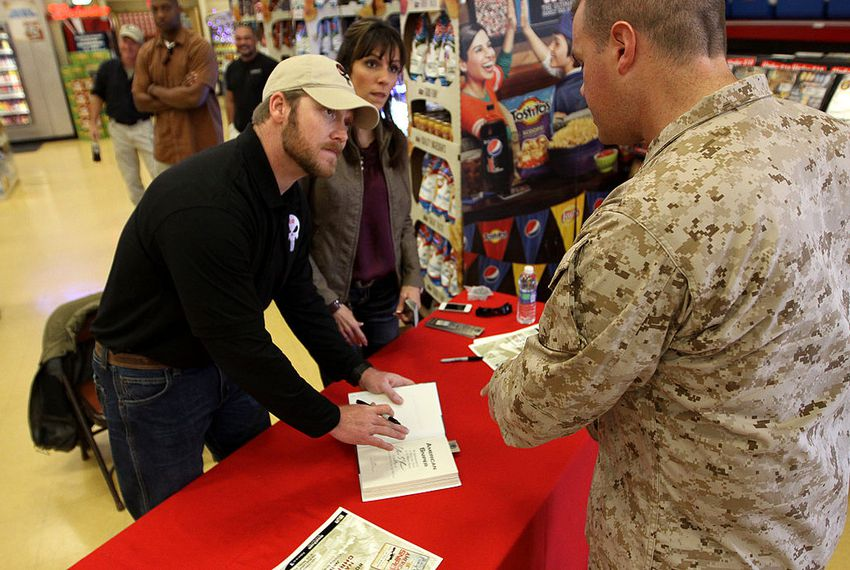 "Navy Seal Sniper Chris Kyle signs a copy of his book ""American Sniper"" for a Camp Pendleton sailor in 2012."
