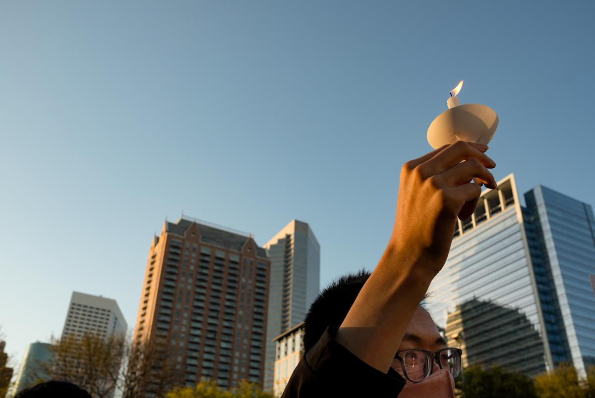 A person holds a candle skyward during a rally at Discovery Green on March 20, 2021, in Houston. People gathered for the Stop Asian Hate Vigil and Rally after a man killed eight, including six Asians, in a mass shooting at three Atlanta spas.