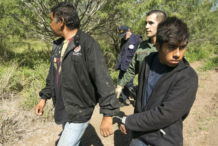 Border Patrol Agent Roberto Rodriguez escorts two Mexican nationals apprehended near the Texas-Mexico border on Oct. 12, 2...