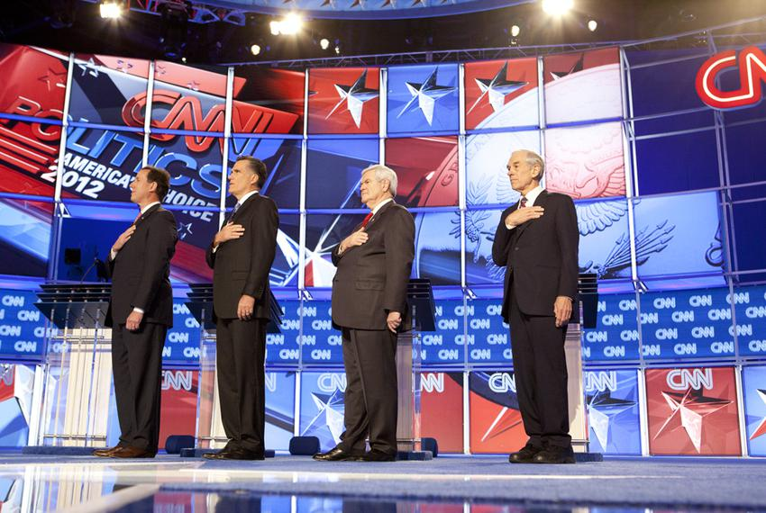 Republican candidates, left to right, Rick Santorum, Mitt Romney, Newt Gingrich and Ron Paul say the Pledge of Allegiance at…