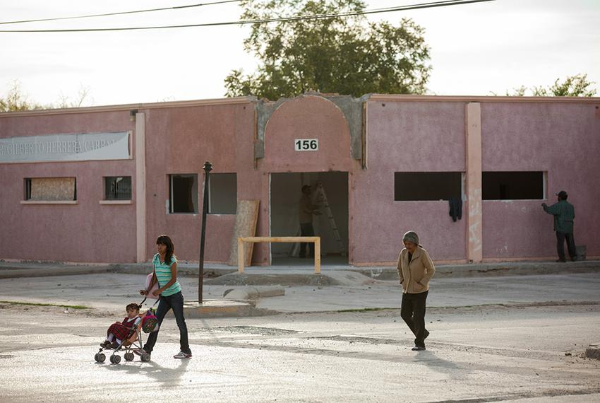 Construction workers are seen as two women walk along the road on an early October morning in Guadalupe Distrito Bravo.