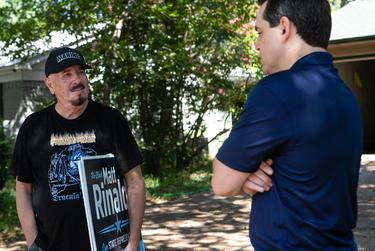 State Rep. Matt Rinaldi speaks with a supporter while delivering yard signs in the Farmers Branch area of Texas House District 115 on August 29, 2018.