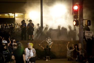 Austin police officers look towards protesters after firing tear gas at the crowd. Protesters would run under the Interstate 35 overpass crouch down in front of the police officers. May 30, 2020.