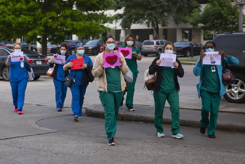 Memorial Hermann Southeast employees are greeted by dozens of people honking their horns and flashing their lights in appr...