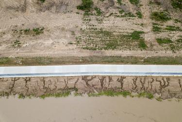 Photos taken after Hurricane Hanna show gullies and rills along a section of the fence that extend toward the river. In some areas, there are holes more than 10 feet wide that expose the footing.