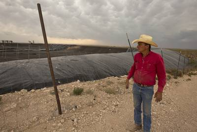 "Rancher and land owner Sonny Lindsay walks next to a ""frac pit"" on land he has leased to ConocoPhillips along Ranch Road 652 near the Texas-New Mexico border."