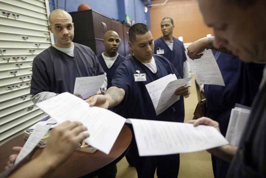 An inmate returns tests to his peers during a break from class. Inmates are regularly tested as a part of their academic bus…