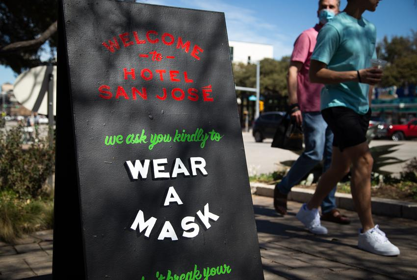 A sign outside of Hotel San Jose asks customers to wear a mask inside the South Austin business on March 3, 2021.