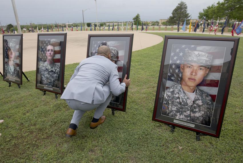 Juan Velez of Chicago kisses the portrait of his daughter, PFC Francheska Velez, who was killed in the November 2009 shootin…