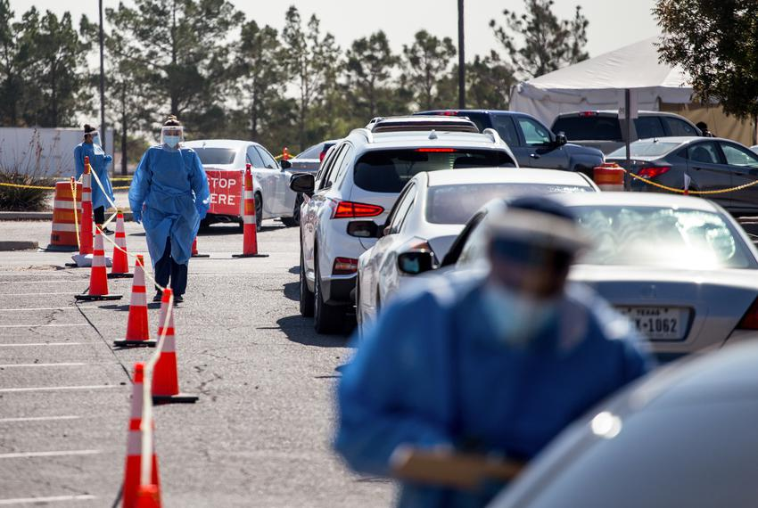 Medical personnel wear personal protective equipment as they register residents waiting in line at a COVID-19 testing site a…