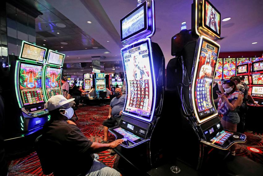 Gamblers play slot machines during the reopening of The D hotel-casino, closed by the state since March 18, 2020, as part of…