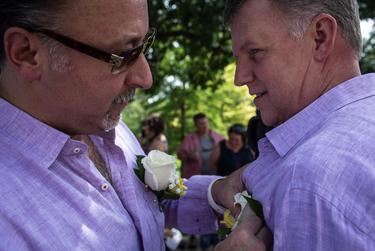 """Donn Gauger and Maxx Judd, who have been together for 11 years, fix each other's boutonnieres prior to the """"Big Gay Wedding"""" ceremony that united over 40 same-sex couples on the south lawn of the Texas State Capitol in Austin on July 4, 2015."""
