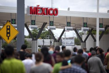 A group of migrants walk across International Bridge Two into Mexico from the United States. The group requested asylum in the United States, but were returned to Mexico to await their court proceedings. July 23, 2019.