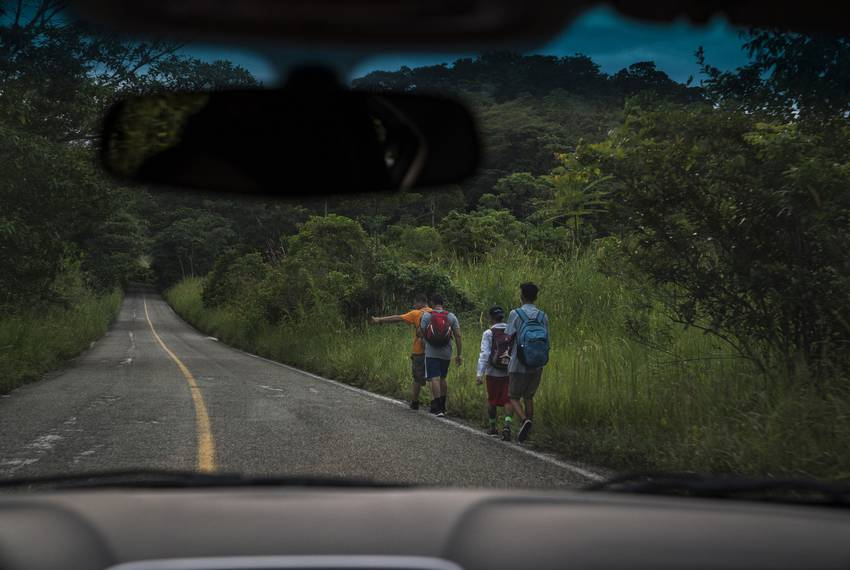 "Migrants walk through Highway México 307 on Oct. 21 near Palenque, Chiapas. The highway is also known by the locals as 'El gran corredor del pacífico del migrante,"" or ""The Great Pacific Corridor of the Migrant."" This is a common route for Honduran migrants due to the proximity to their country."