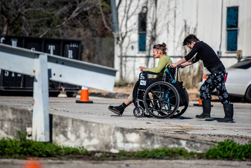 Amy T. pushes Pam Reynolds to her camping location on Jan. 23, 2020 at a state-sanctioned homeless camping site in Austin....