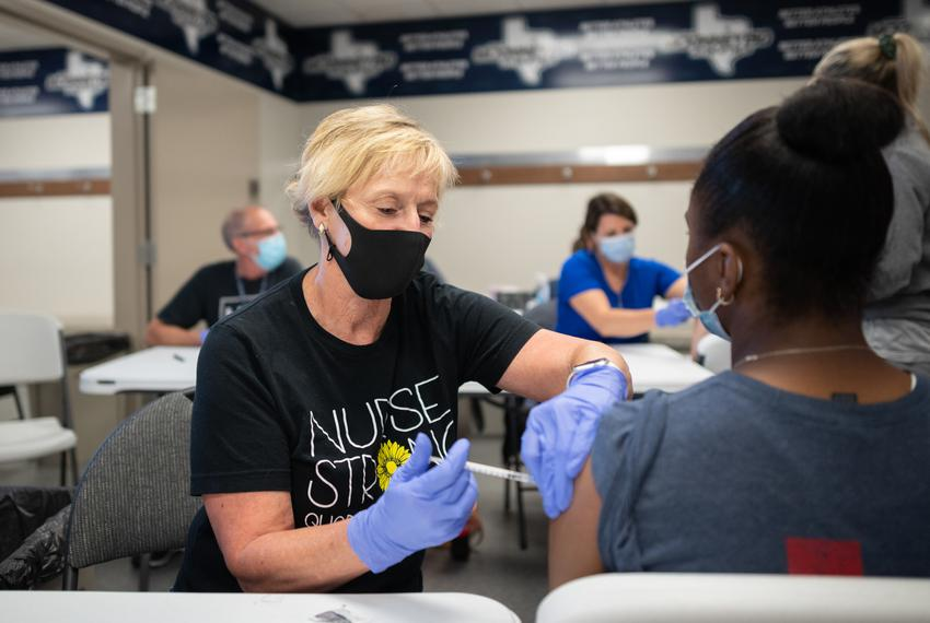 McKinney ISD registered nurse Nancy Yarbrough administers a COVID-19 vaccine to a student at McKinney ISD Stadium and Commun…