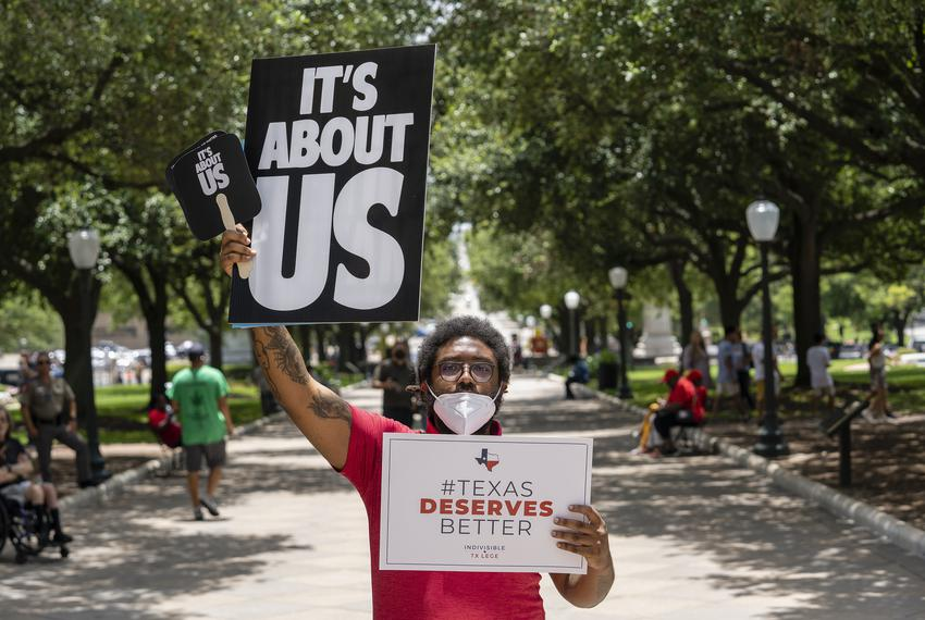 Tevin English holds signs in front of the Texas Capitol at a Voting Rights Advocacy Day rally held by various voting rights …