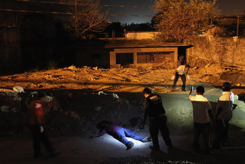 A forensics team inspects the body of a man killed in a suspected drug-related execution along the path where he was shot ...