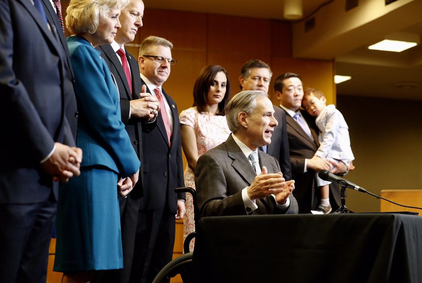 Gov. Greg Abbott signs four bills aimed at reforming Child Protective Services, at the Texas Department of Family and Protective Services headquarters in Austin on May 31, 2017.