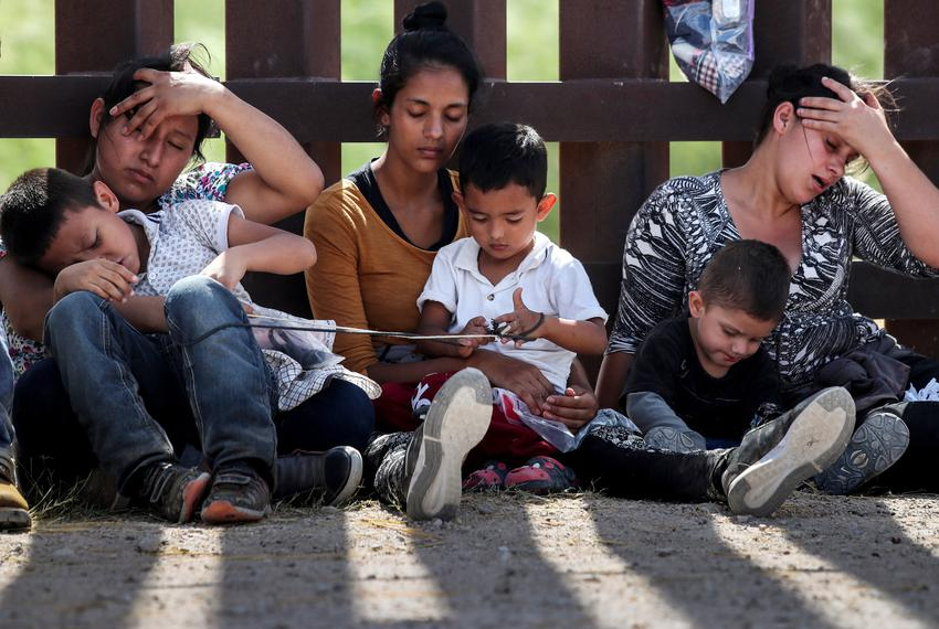 Immigrant women hold their children along the border wall as they await apprehension after illegally crossing into the U.S. …