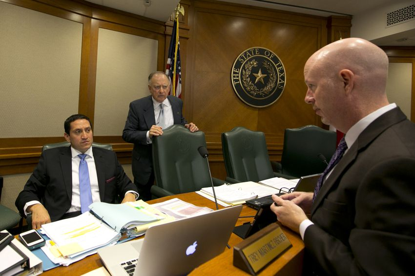 Rep. Trey Martinez Fischer, D-San Antonio, and Rep. Dan Flynn, R-Canton, speak with a lawyer during a break at a House Committee on Transparency in State Agency Operations hearing on October 23rd, 2013
