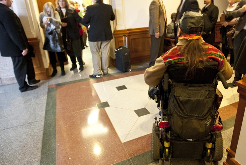 Disabled man outside room where Senate Finance Committee listens to testimony on February 2, 2011