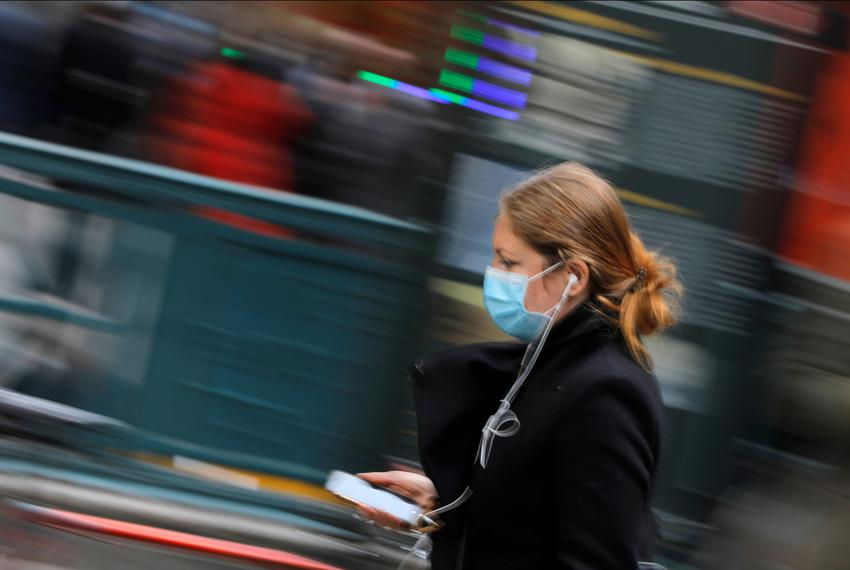 A woman in a face mask walks in the downtown area of Manhattan, New York City, after further cases of coronavirus were con...